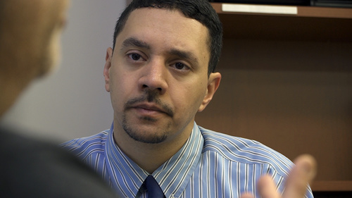 A man with short black hair and a goatee listening to a speaker
